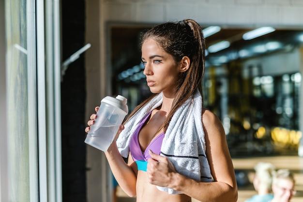 水のボトルを押しながらトラフウィンドウを探して首にタオルで美しい白人のスポーティな女性。ジムのインテリア。