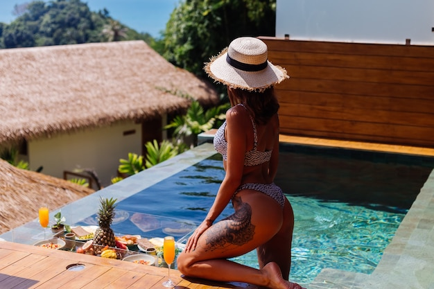 Bella donna abbronzata caucasica in bikini e cappello di paglia con colazione galleggiante in incredibile villa di lusso in stile bali al giorno pieno di sole in piscina, sfondo tropicale.