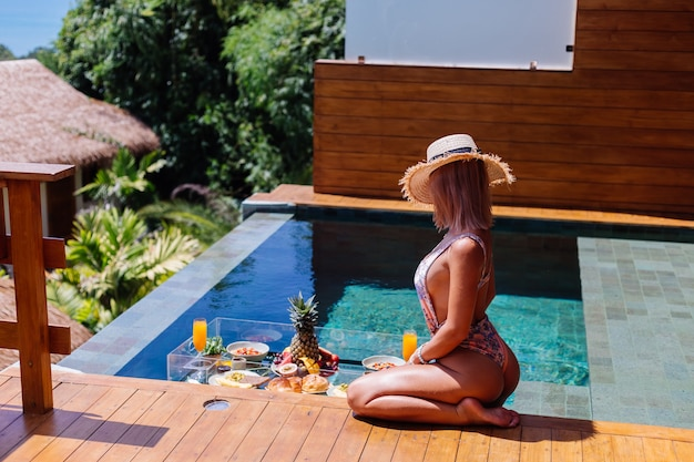 Beautiful caucasian tanned woman in bikini and straw hat with floating breakfast at amazing luxury bali style villa at sunny day by swimming pool, tropical background.