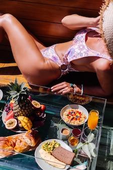 ビキニと麦わら帽子の美しい白人の日焼けした女性、スイミングプール、熱帯の背景のそばの晴れた日に素晴らしい豪華なバリスタイルのヴィラでのフローティング朝食。