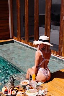 Красивая кавказская загорелая женщина в бикини и соломенной шляпе с плавающим завтраком на удивительной роскошной вилле в стиле бали в солнечный день у бассейна, на тропическом фоне.