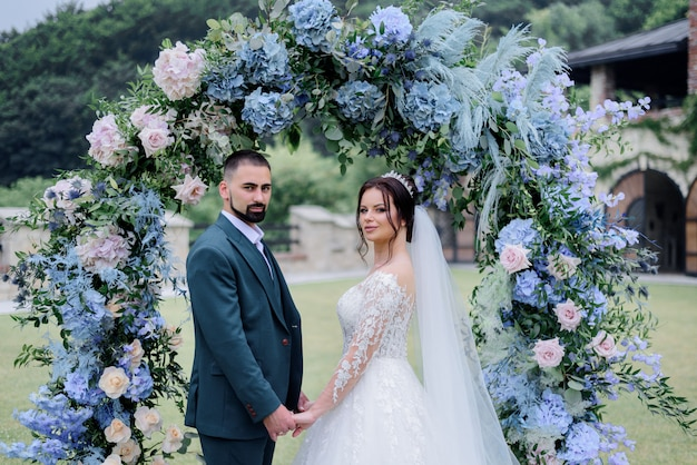 青いアジサイのアーチで飾られ、一緒に手を繋いでいるの前に美しい白人の結婚式のカップルが立っています。