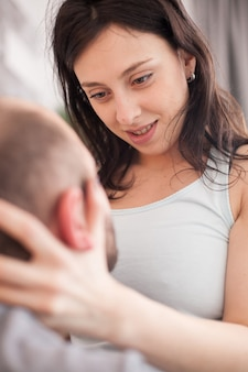 Beautiful caucasian wife in pajamas looking with passion into her husband eyes after waking up.