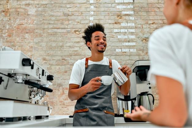 아름 다운 백인 여자와 앞치마 유니폼을 입고 아프리카 바리 스타 남성은 카페테리아에서 채팅과 웃음, 커피를 만들고 있습니다.