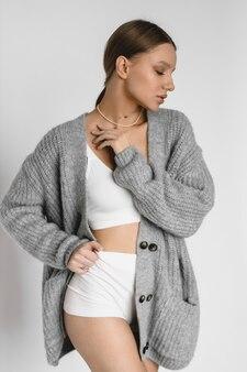 백색 란제리와 흰색 배경에 스웨터에 아름 다운 백인 여자 선수.