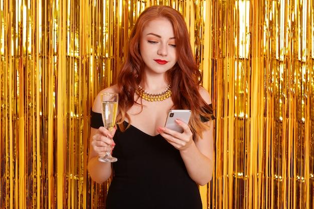Bella donna caucasica chat sul telefono e bere vino, sembra concentrata, signora dai capelli rossi con bigodini in piedi isolato su orpelli dorati, donna con smart phone.