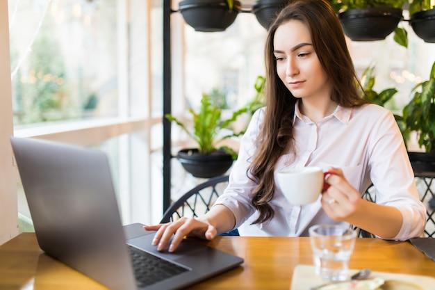 Красивая кавказская женщина мечтает о чем-то, сидя с портативным нетбуком в современном кафе-баре. молодая очаровательная женщина-фрилансер думает о новых идеях во время работы на портативном компьютере