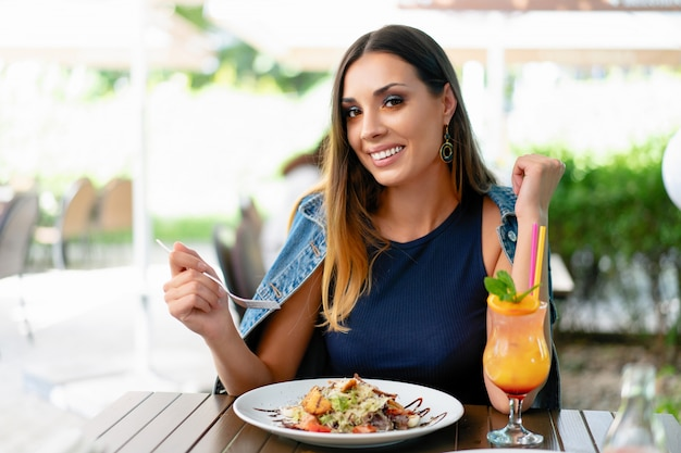 サラダを食べて、エキゾチックな夏のカクテルを飲む美しい白人女性