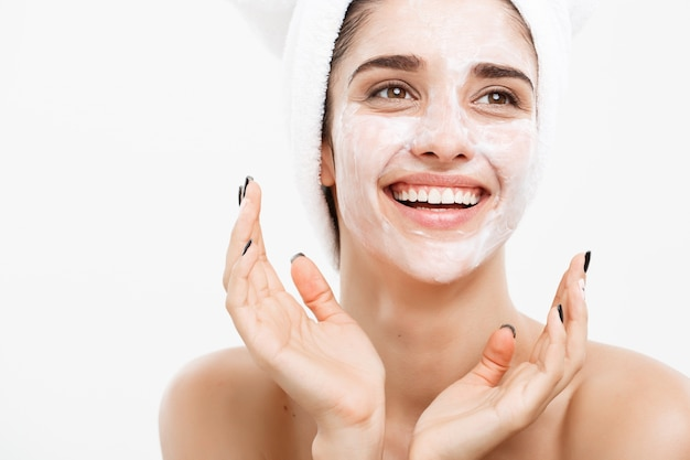 Beautiful caucasian woman face portrait applying cream mask on her facial skin white background.