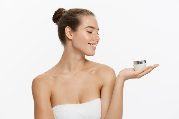 Beautiful caucasian woman face portrait holding and presenting cream tube product.