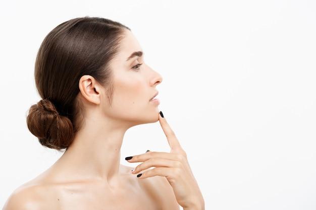 美しいコーカサス人の女性の顔の肖像画は、彼女の顎を指で触ってショックを受け、心配しているにきびと白くする。