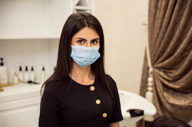 美しい白人女性の美容師は、職場で安全保護医療マスクを着用しています