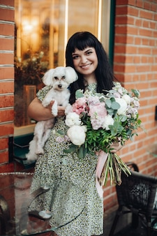 Beautiful caucasian woman holding her white dog and flowers