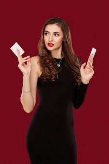 Красивая кавказская женщина в черном платье с покерными картами, играющими в казино