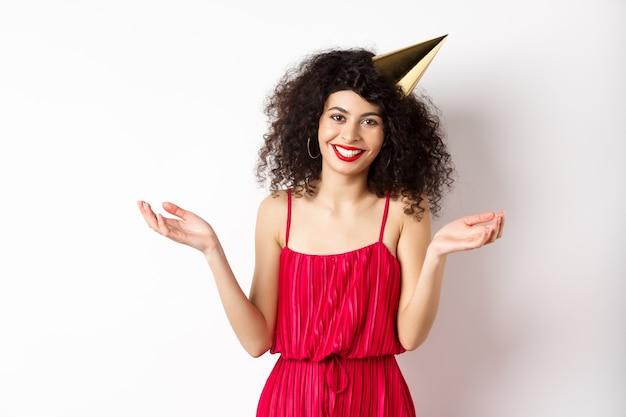 赤いドレスを着て、休日を祝って、パーティーハットをかぶって笑って、白い背景の上に立っている美しい白人女性。コピースペース