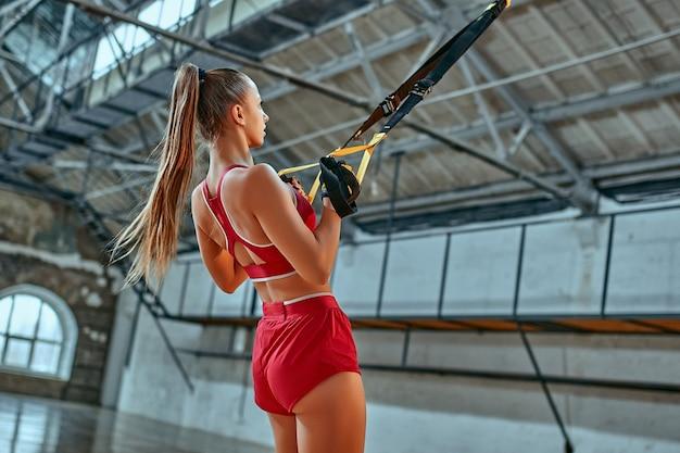 ジムでtrxフィットネスベルトとスポーツウェアの列車の美しい白人女性。筋肉のスリングや吊りストラップを行使する美しい女性。
