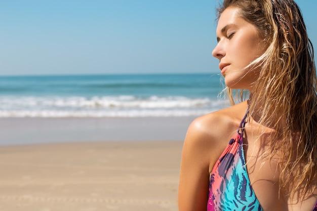 コピースペースと熱帯のビーチで水着姿の美しい白人女性。自然の美しさ、スキンケア、若い女性は目を閉じて横を向いています。休暇を楽しんでいる日焼けした女の子。