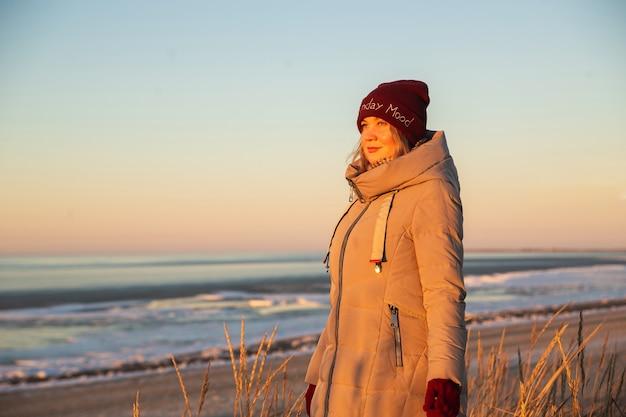 겨울 바다의 배경에 태양을 찾고 겨울 옷에 아름 다운 백인 여자. 바다, snunny 바람이 부는 날씨, 대기 이미지에 여자의 초상화. 도피주의, 자연과의 조화.