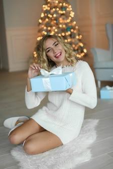 美しい白人女性がギフトボックスを開梱しています。年末年始、クリスマス、冬休み