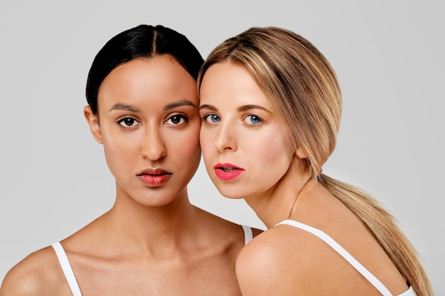Красивая кавказская женщина полагаясь к ее афро-американскому другу, концепция красоты