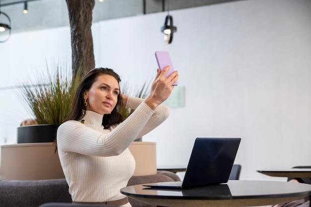 Красивая кавказская женщина делает селфи на смартфоне, сидя за столом с ноутбуком у блогера