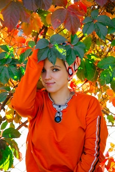 Beautiful caucasian woman in orange hoodie among autumn colorful leaves. people in autumn time concept.