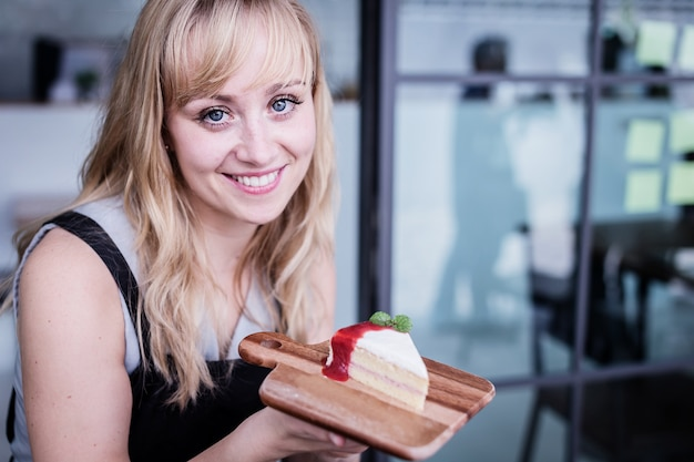 Beautiful caucasian woman presenting yummy cake on wooden tray