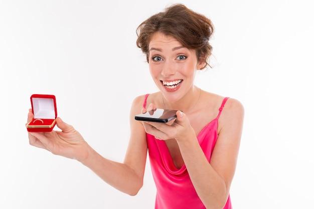 Красивая кавказская женщина говорит о предложении руки и сердца с телефоном, картина изолированная на белой стене
