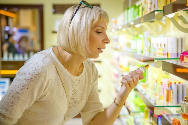 Beautiful caucasian woman selecting perfume