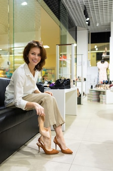 ソファーに座っている美しい白人女性とエレガントな靴を試着