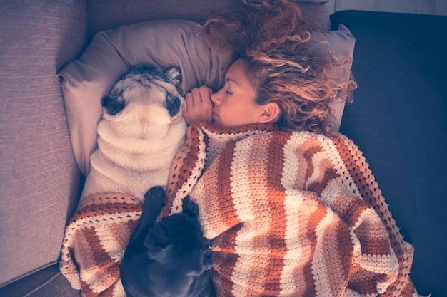 Красивая кавказская женщина спит дома зимой с двумя лучшими друзьями, собачьи мопсы вместе ложатся с любовью. концепция защиты и дружбы в коричневых тонах и тонах. вид с высоты птичьего полета