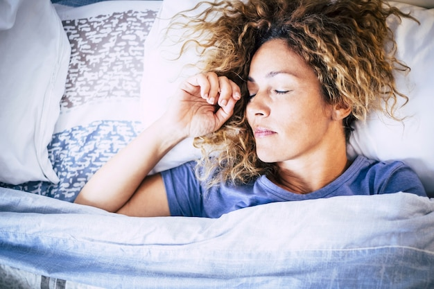 美しい白人女性がベッドで朝の光で眠る-人々のための寝室の睡眠活動-疲れた女性の概念と家やホテルでリラックス