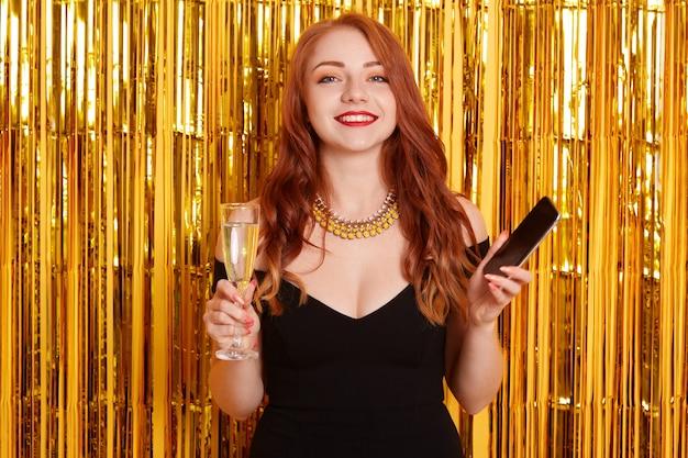 美しい白人女性が手に携帯電話と白ワインを飲みながら笑顔