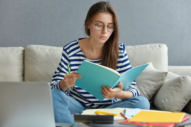 Beautiful caucasian woman in striped sweater and spectacles, concntrated on homework, poses at comfortable couch in modern apartment, uses laptop computer for chatting online, poses at home.