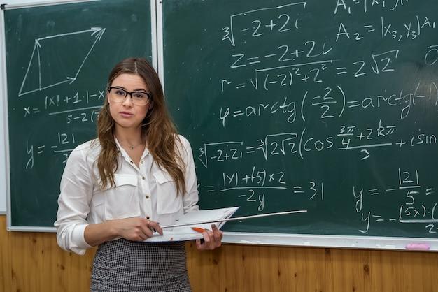 칠판 근처 교실에 서 있는 아름 다운 백인 여자 교사. 교육. 학교