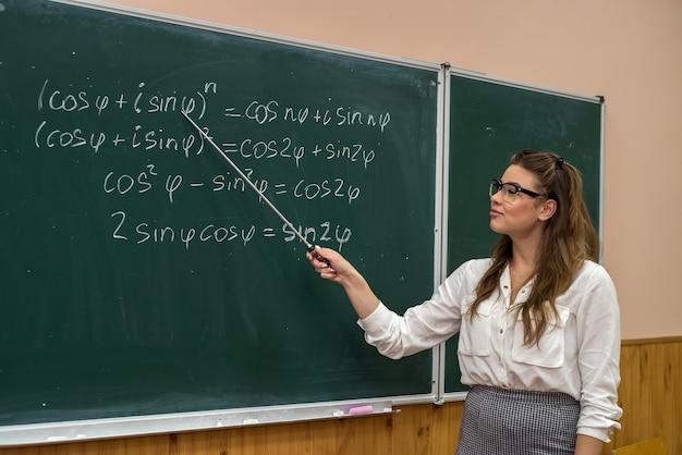 黒板の近くの教室に立っている美しい白人女性教師。教育。学校