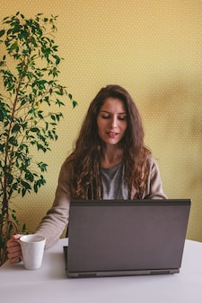 Beautiful caucasian woman using laptop and drinking coffee