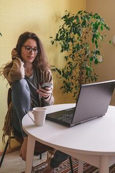 아름 다운 백인 여자 휴대 전화를 사용하고 노트북과 커피 컵과 테이블에 앉아