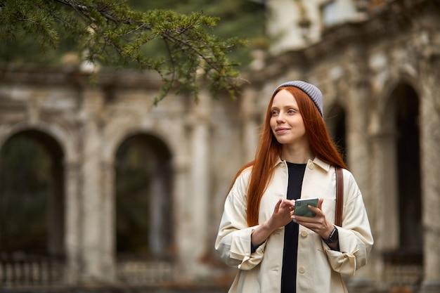 スマートフォンの大人の女性のtravを使用して朝に歴史的な場所を歩いている美しい白人女性...