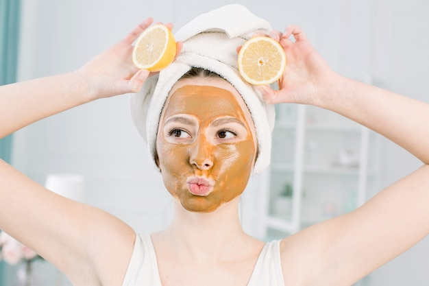 Beautiful caucasian woman in white towel with brown clay mask on her face and lemon slices, showing tongue and kiss face, beauty treatments concept
