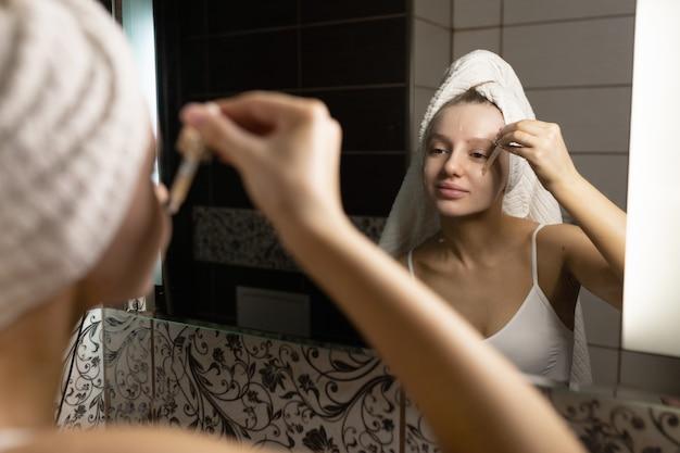 Красивая кавказская женщина с полотенцем на голове в ванной после душа смотрит в зеркало