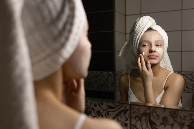 Красивая кавказская женщина с полотенцем на голове в ванной наносит крем после душа на лицо и улыбается. концепция личной гигиены.