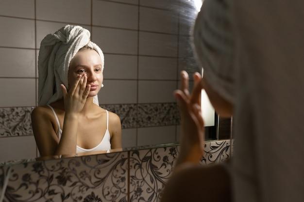 Красивая кавказская женщина с полотенцем на голове в ванной наносит крем после душа на лицо