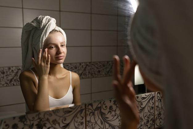 Красивая кавказская женщина с полотенцем на голове в ванной смотрит в зеркало и наносит крем на лицо