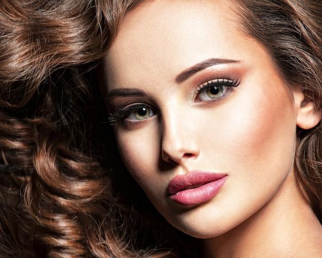 茶色の巻き毛を持つ美しい白人女性。かなり若い大人の女の子の肖像画。灰色の背景の上にスタジオでポーズをとる魅力的な女性のセクシーな顔。