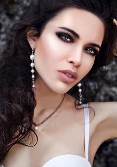 Beautiful caucasian woman with evening makeup and dark long hair outdoors