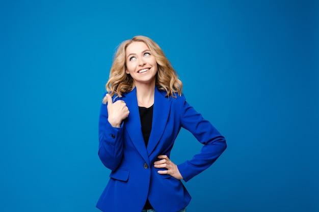 Красивая кавказская женщина с светлыми волнистыми волосами в синем пиджаке любит изолироваться на синем фоне
