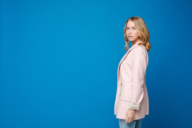 白いシャツと青い背景で隔離の青いズボンの明るいウェーブのかかった髪を持つ美しい白人女性