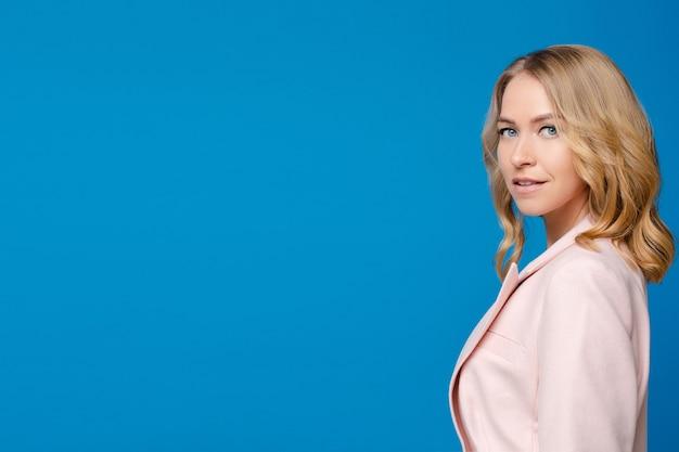 青い背景で隔離の白いシャツの明るいウェーブのかかった髪を持つ美しい白人女性