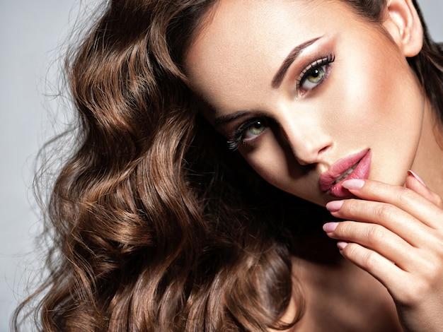 Bella donna caucasica con capelli ricci marroni lunghi. ritratto di una ragazza adulta abbastanza giovane. volto sexy di una donna attraente in posa in studio su sfondo grigio.